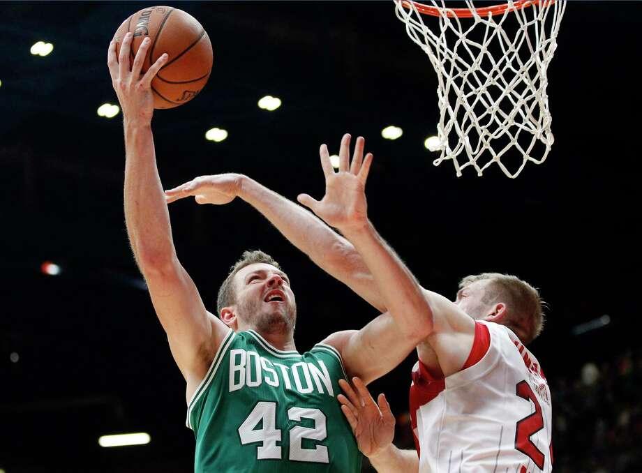 The Boston Celtics' David Lee, left, shoots over Olimpia Milano's Robbie Hummel during Tuesday's exhibition game near Milan, Italy. Photo: Antonio Calanni — The Associated Press   / AP
