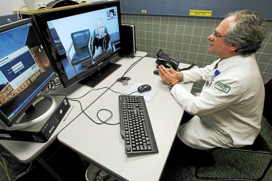 Dr. Terry Rabinowitz, right, talks with nurse Leslie Orelup at Helen Porter Nursing Home in Burlington, Vt. Doctors have used video feeds and other technology for years to treat patients in remote locations. But experts say growing smartphone use and customer demand are fueling a rapid expansion of telemedicine into everyday care the family doctor used to handle. Photo: AP Photo/Toby Talbot, File   / AP