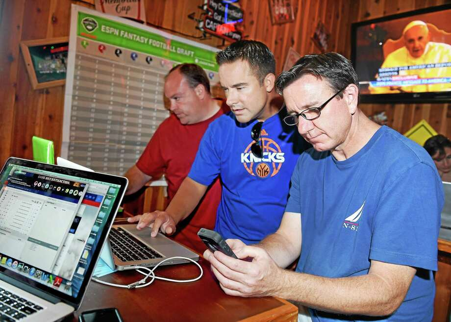 Tom Chelednik (center) of Brookfield assists Scott Champagne (right) of Monroe with some computer problems at a fantasy football party at Hooter's in Milford on 8/31/2015. Photo: (Arnold Gold-New Haven Register)