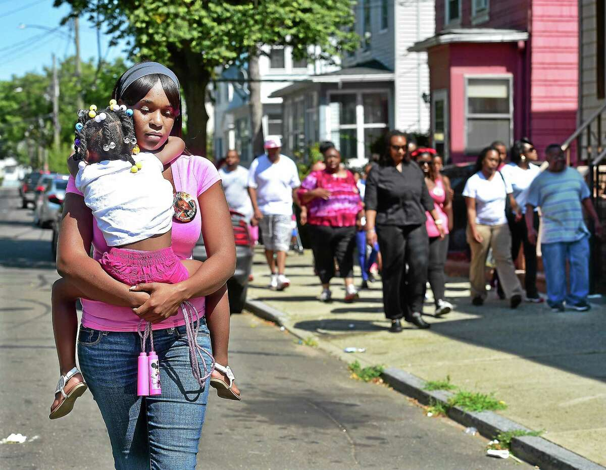 "Shante Howard carries her four-year-old neice Chawnaye Battle walking alongside a march organized by New Haven resident Ira Johnson, Saturday, August 8, 2015. Howard marched in response to her 25-year-old cousin Francesca ""Lala"" Ratchford, who was fatally shot at 4:03 a.m. July 27, 2015 on the porch of her Congress Avenue home in the city's Hill section."