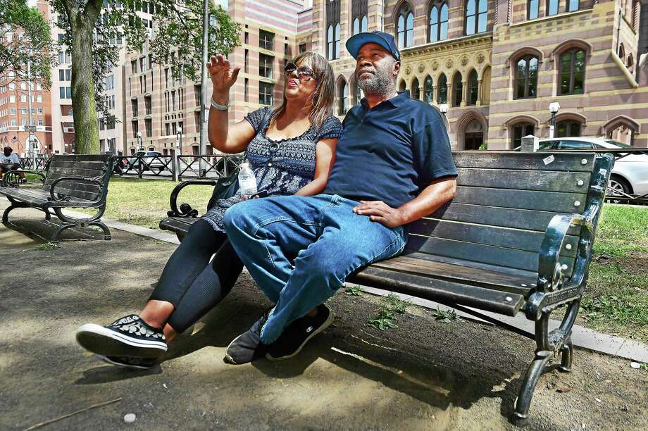 Jesse Jhop Hardy and Sherell Nesmith, the sister of murder victim Ray Roberson, sit on the bench on the New Haven Green, Saturday, August 8, 2015. Roberson, the New Haven man who was found dismembered last month, told Hardy, a life-long childhood friend he favored that certain bench with City Hall in the background because it was on the ìpeacefulî side of the green, compared to the upper green where the rowdier crowd hangs out. He said Roberson would take a nip of alcohol and go to sleep. Photo: (Catherine Avalone - New Haven Register)     / New Haven RegisterThe Middletown Press