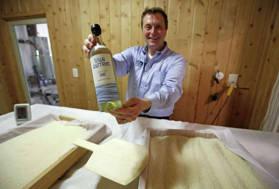 """Dan Ford, founder of the Blue Current Brewery, poses with a bottle of sake at the brewery in Kittery, Maine. Steamed rice is inoculated in a sauna-like koji room for two days as part of the six-week brewing process to make """"rice wine."""" Photo: Photos By Robert F. Bukaty — The Associated Press   / AP"""