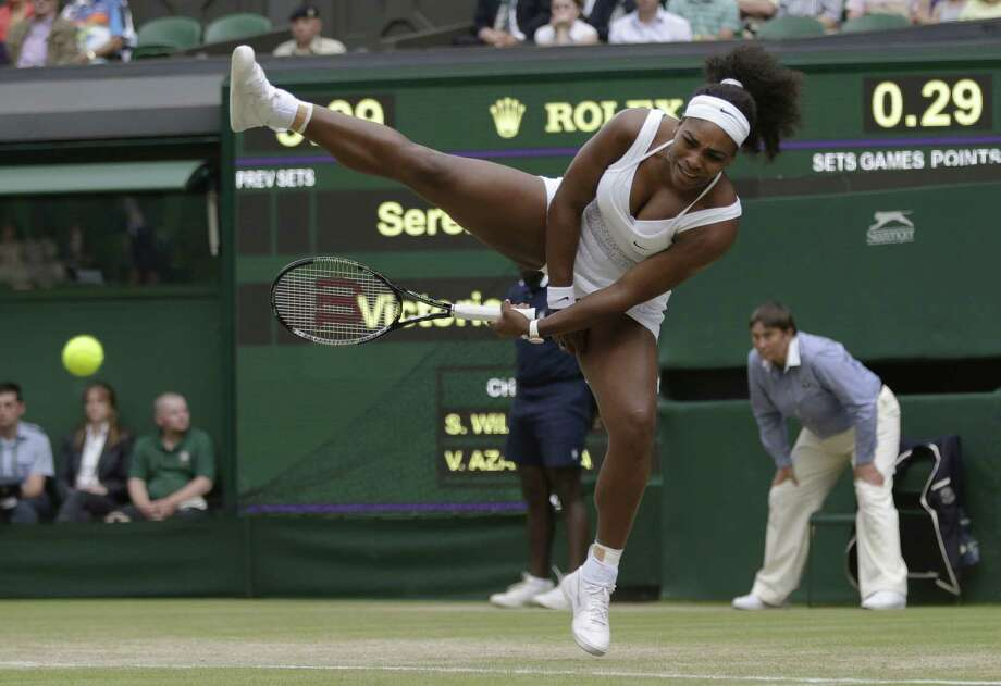 Serena Williams returns the ball to Victoria Azarenka during their singles match on Tuesday at the All England Lawn Tennis Championships in Wimbledon, London. Photo: Pavel Golovkin — The Associated Press   / AP
