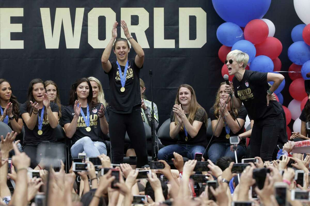 U.S. women's soccer midfielder Megan Rapinoe, right, introduces teammate Carli Lloyd during a public rally held to celebrate the team's World Cup championship on Tuesday in Los Angeles.