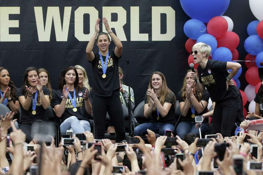 U.S. women's soccer midfielder Megan Rapinoe, right, introduces teammate Carli Lloyd during a public rally held to celebrate the team's World Cup championship on Tuesday in Los Angeles. Photo: Jae C. Hong — The Associated Press   / AP