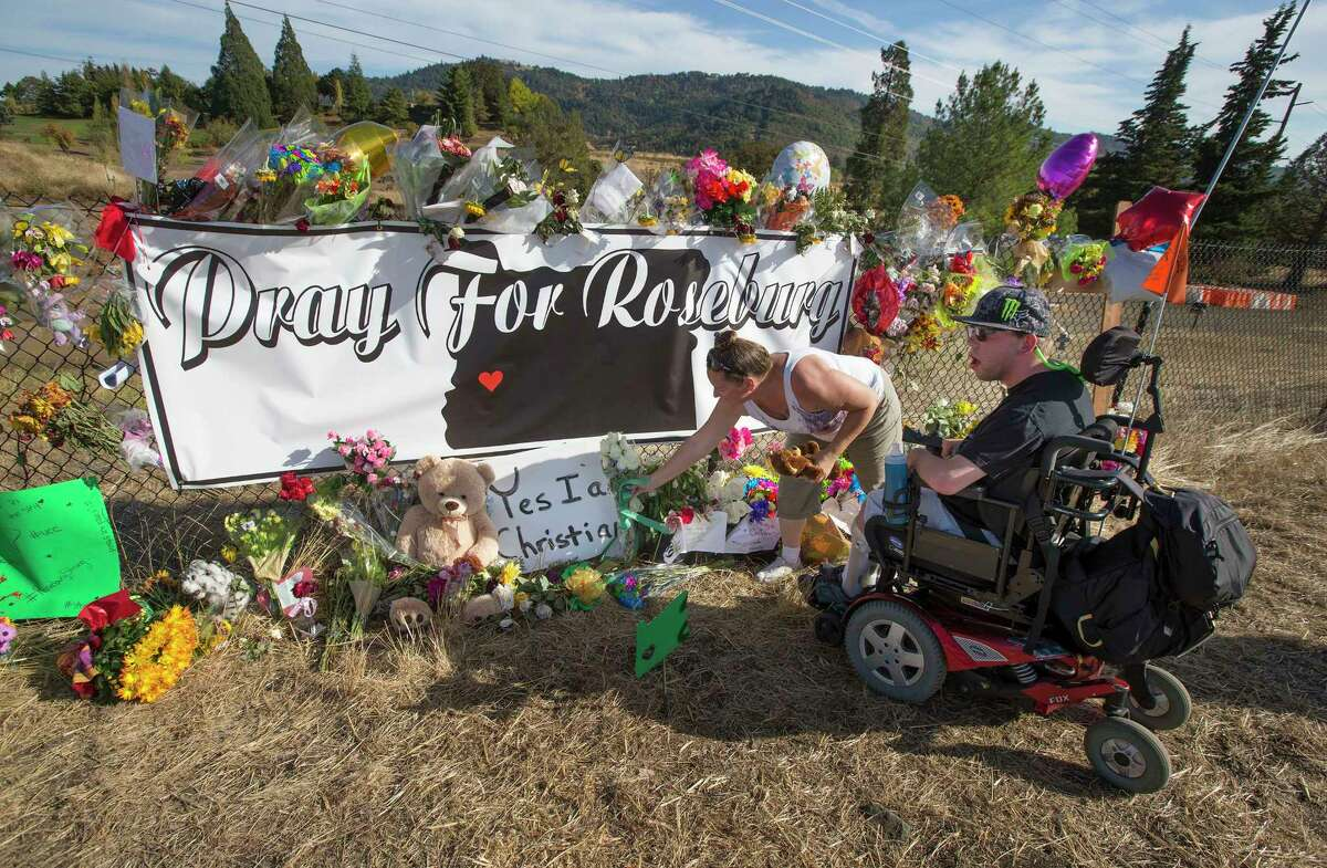 Candida Miller, left, and Brandon Snyder leave flowers at a site of a growing memorial to victims of the mass shooting at Umpqua Community College in Roseburg, Ore. on Oct. 6, 2015.