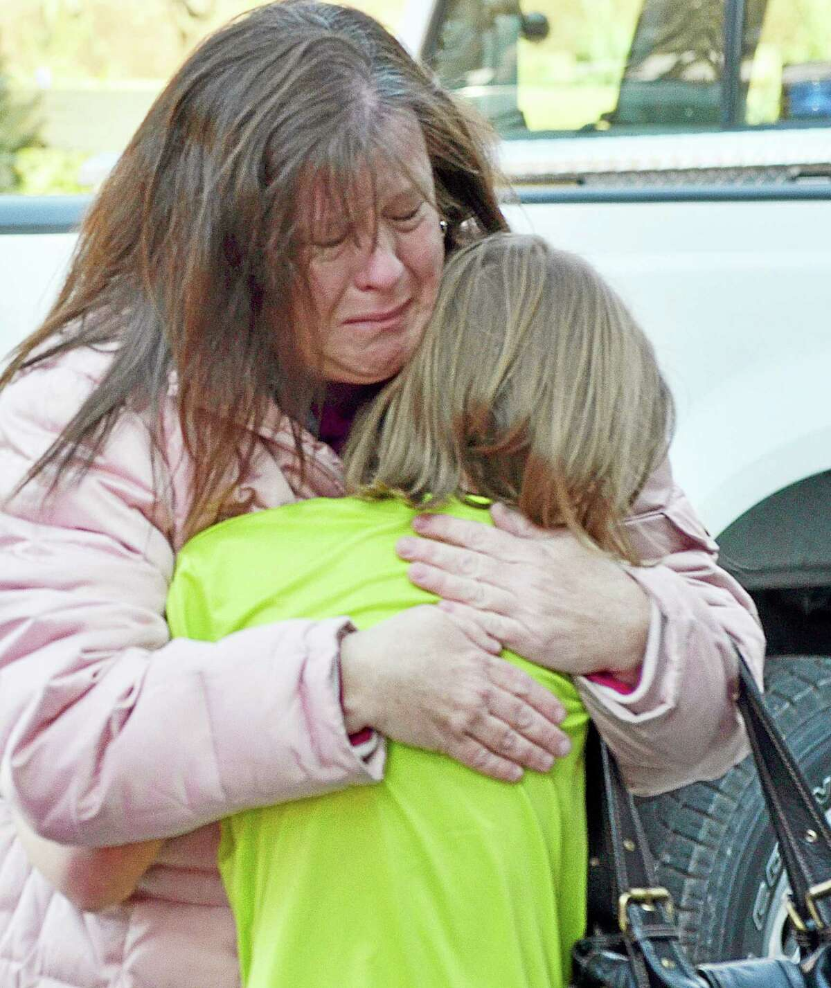 A mother hugs her daughter following a shooting at the Sandy Hook Elementary School in Newtown, Conn. on Dec. 14, 2012.