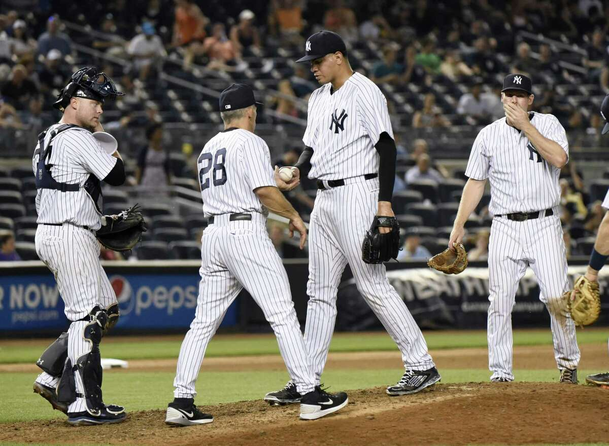 Yankees pitcher Dellin Betances hands the ball to manager Joe Girardi (28) as catcher Brian McCann, left, and third baseman Chase Headley watch as Betances leaves the game after giving up a home run in the 10th inning against the Oakland Athletics.