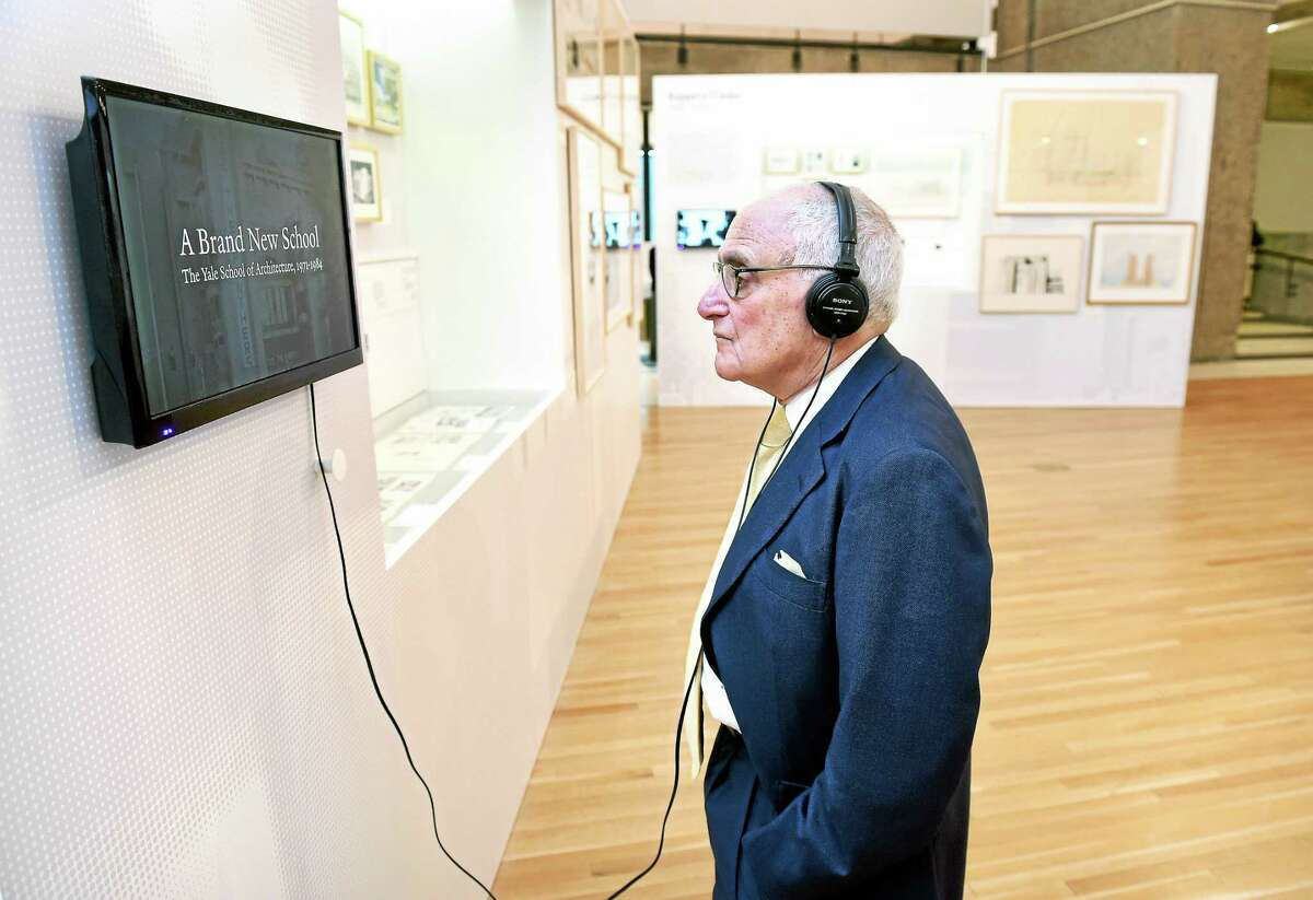 """Dean of the Yale School of Architecture Robert A.M. Stern listens to an audio recording at the opening of """"Pedagogy and Place, Celebrating 100 Years of Architecture Education at Yale"""" in Paul Rudolph Hall at Yale."""