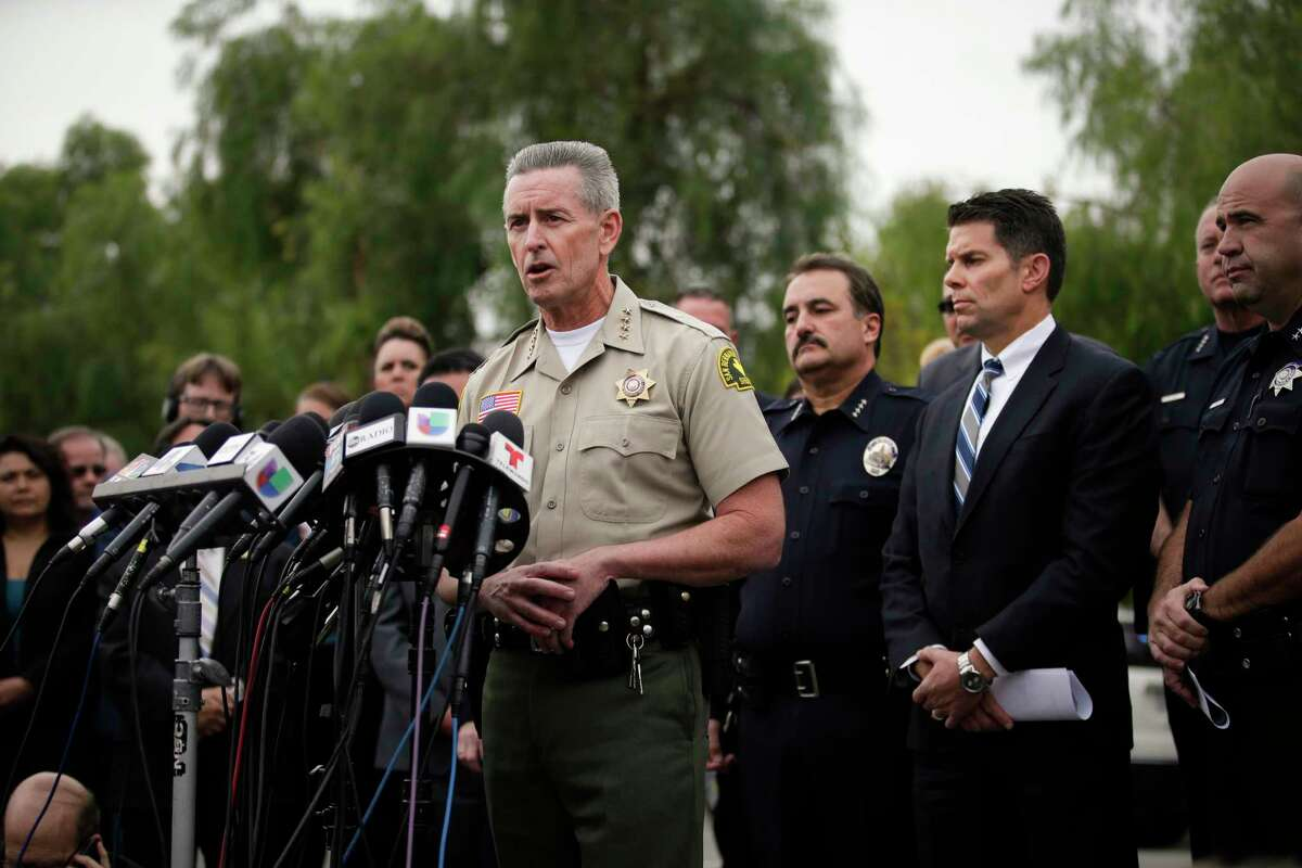 San Bernardino County Sheriff John McMahon, center, talks to reporters during a news conference Friday, Dec. 4, 2015, in San Bernardino, Calif. The FBI said Friday it is officially investigating the mass shooting in California as an act of terrorism, while a U.S. law enforcement official said the woman who carried out the attack with her husband had pledged allegiance to the Islamic State group and its leader on Facebook.