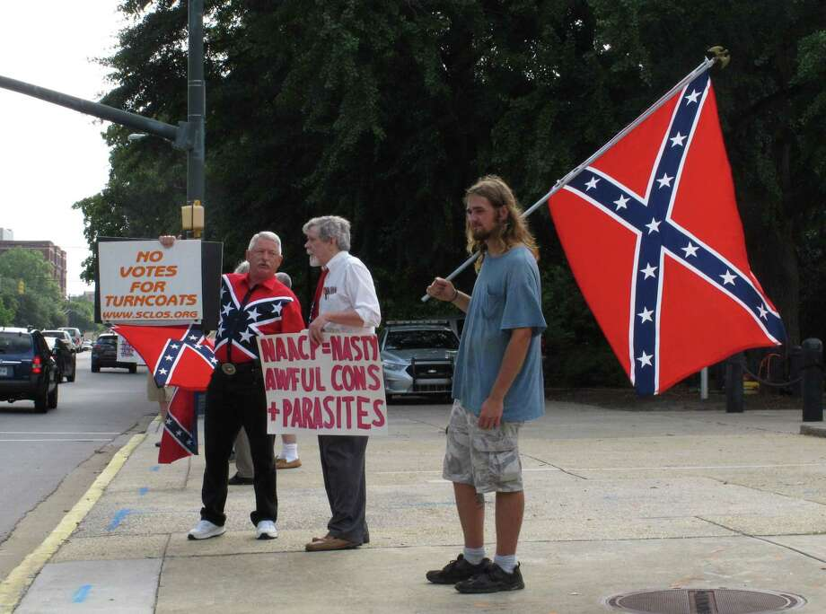 William Cheek, left, Nelson Waller, center, and Jim Collins, right, protest proposals to remove the Confederate flag from the grounds of the South Carolina Statehouse on Monday, July 6, 2015, in Columbia, S.C. The General Assembly returns Monday to discuss Gov. Nikki Haley's budget vetoes and what to do with the rebel flag that has flown over some part of the Statehouse for more than 50 years. (AP Photo/Jeffrey Collins) Photo: AP / AP