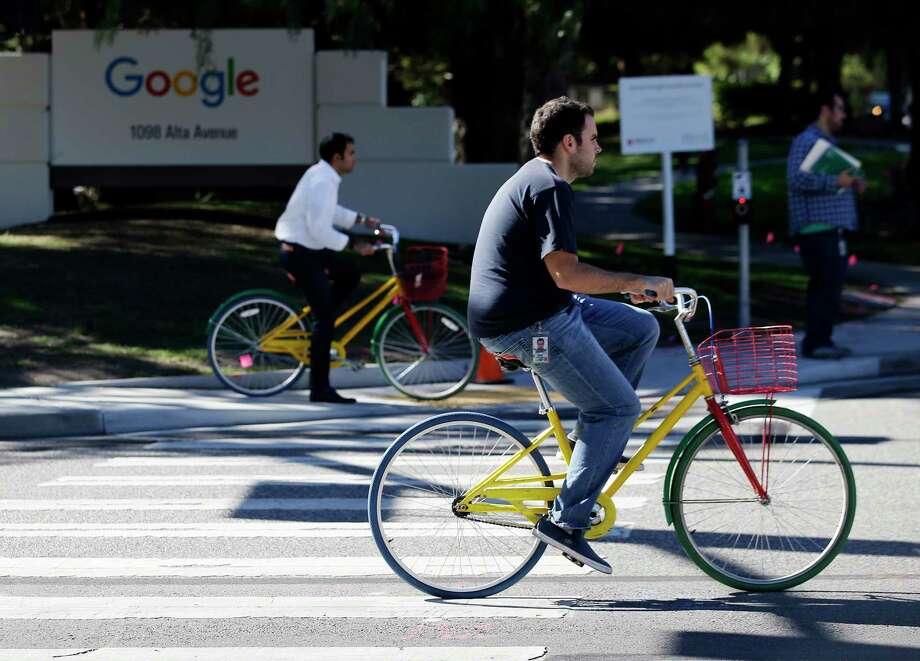 Employees ride company bicycles outside Google headquarters in Mountain View, Calif. Photo: AP Photo/Marcio Jose Sanchez   / AP
