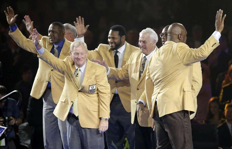 Members of the Pro Football Hall of Fame Class of 2015 wave to the crowd after receiving their gold jackets on Thursday during the enshrinees' dinner in Canton, Ohio. Photo: Scott Heckel — The Repository   / The Repository