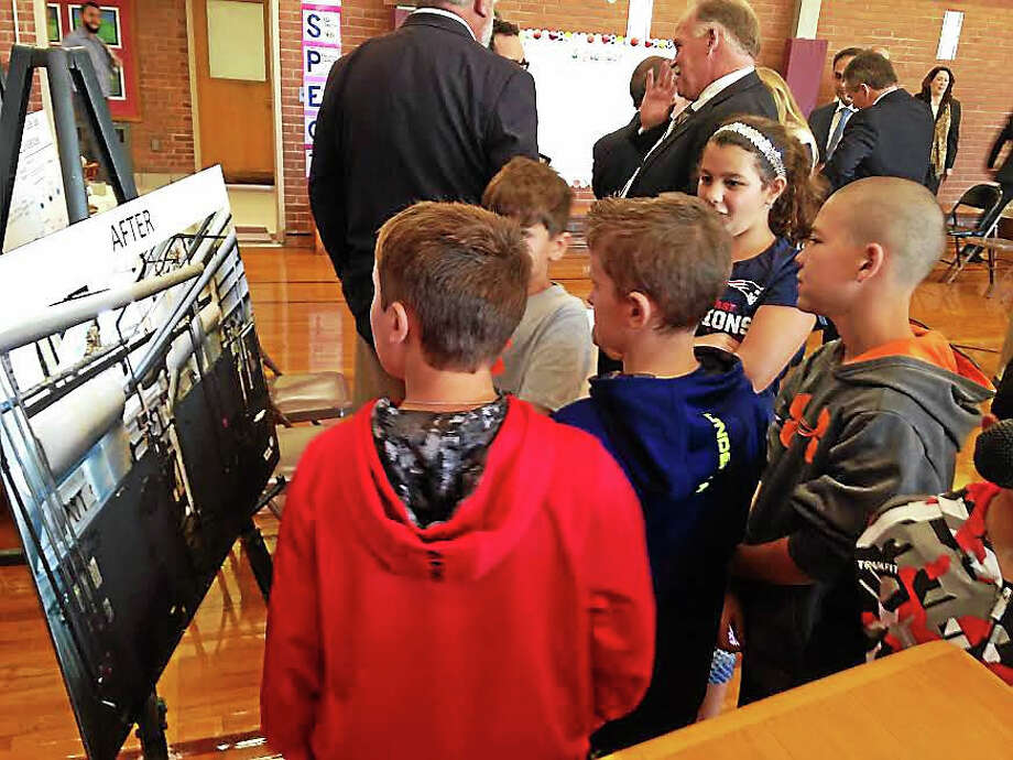 Fifth-graders at Montowese School look at before and after pictures of the recently-replaced school boilers, part of a program that will save the town $6 million in energy-related infrastructure upgrades to be completed by next summer. Photo: Kate Ramunni — New Haven Register