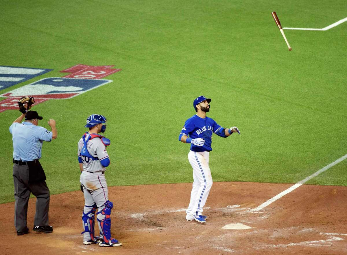 The Blue Jays' Jose Bautista flips his bat to celebrate his three-run home run during Game 5 of the ALDS against the Texas Rangers in Toronto.