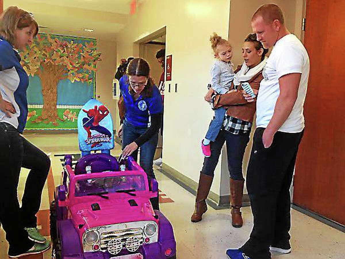 CCSU associate professor Michele Dischino presents a motorized toy car to Cameron Werdann, 4, and parents Lisa and Brian Friday afternoon.