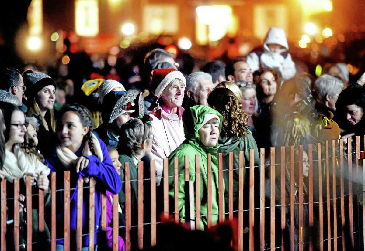 People watch dance and musical performances before Friday's Christmas tree lighting on the Guilford Green.