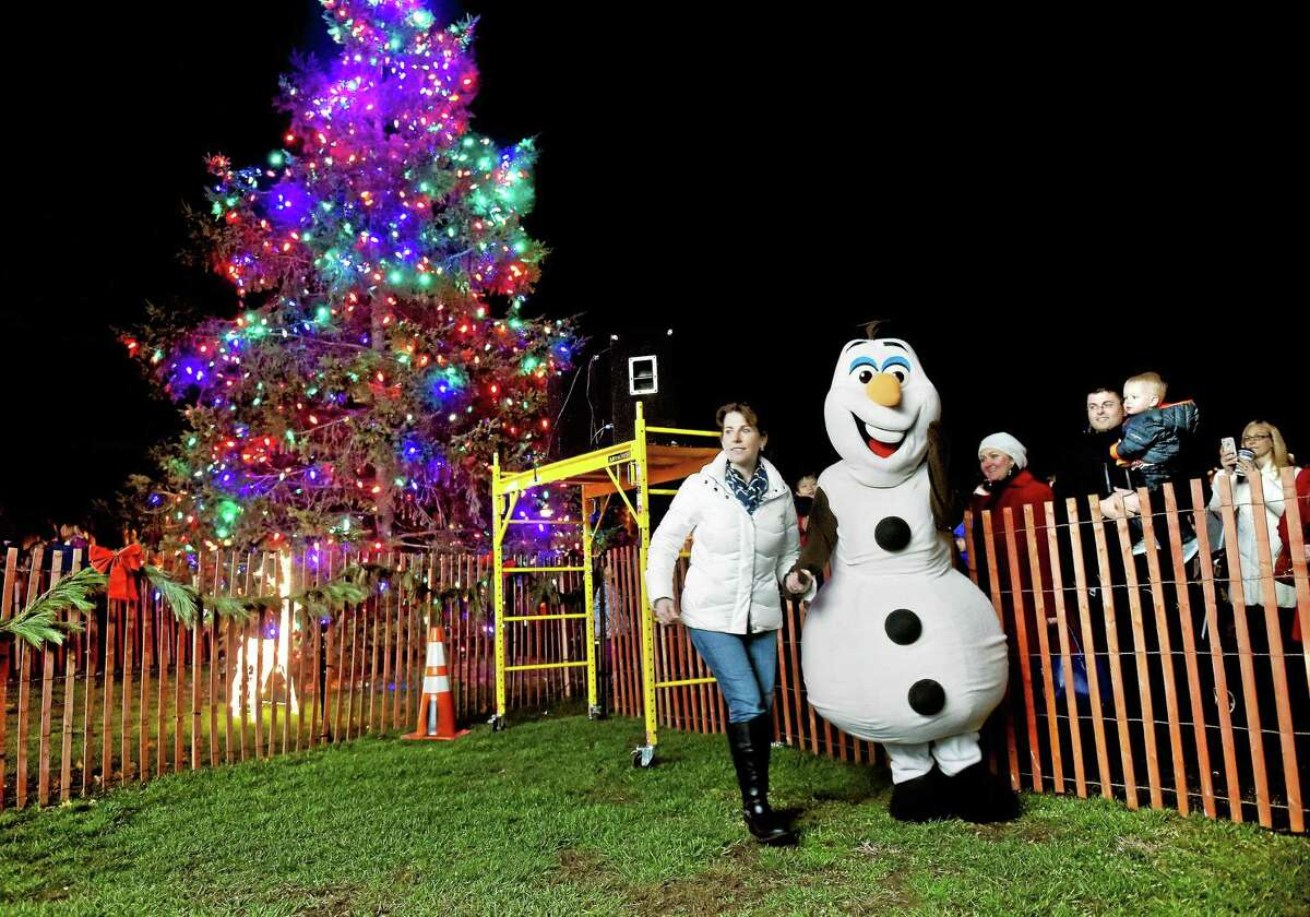Michelle Call, left, leads Anna Munafo as Olaf during the Christmas tree lighting on the Guilford Green Friday.