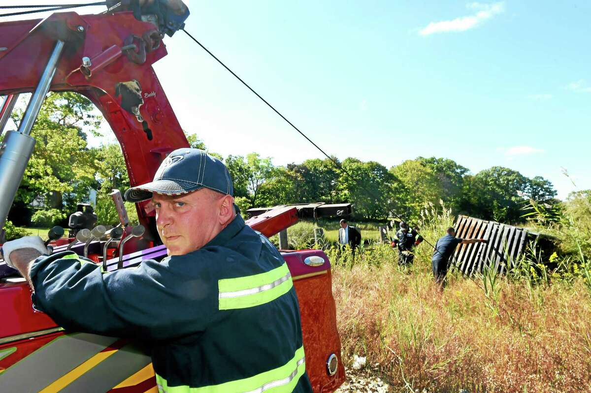 Robert Bruneau of Bruneau's Garage of West Haven, left, with the help of his employees Kylee Yu and Victor Guadalupe, donates time and his tow truck to pull a large metal Dumpster out of the Oyster River marsh behind the Family Dollar store near Ocean Avenue in West Haven Wednesday.