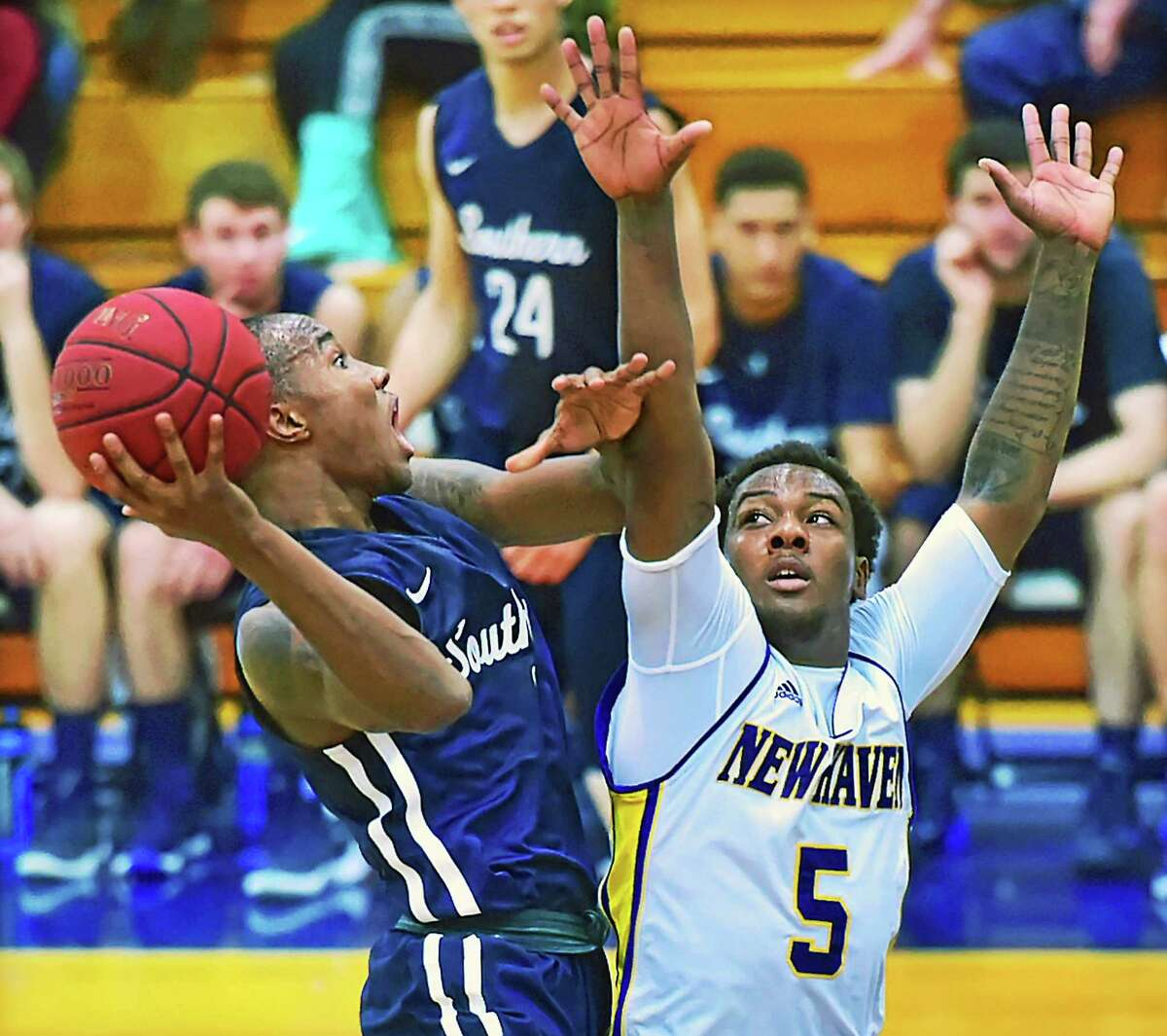 (Catherine Avalone - New Haven Register) SCSU's freshman guard Isaiah McLeod elevates for a shot as UNH junior guard Jemal Mosley defends, Wednesday, December 2, 2015 at the Charger Gymnasium at the University of New Haven. The Chargers won, 80-60.