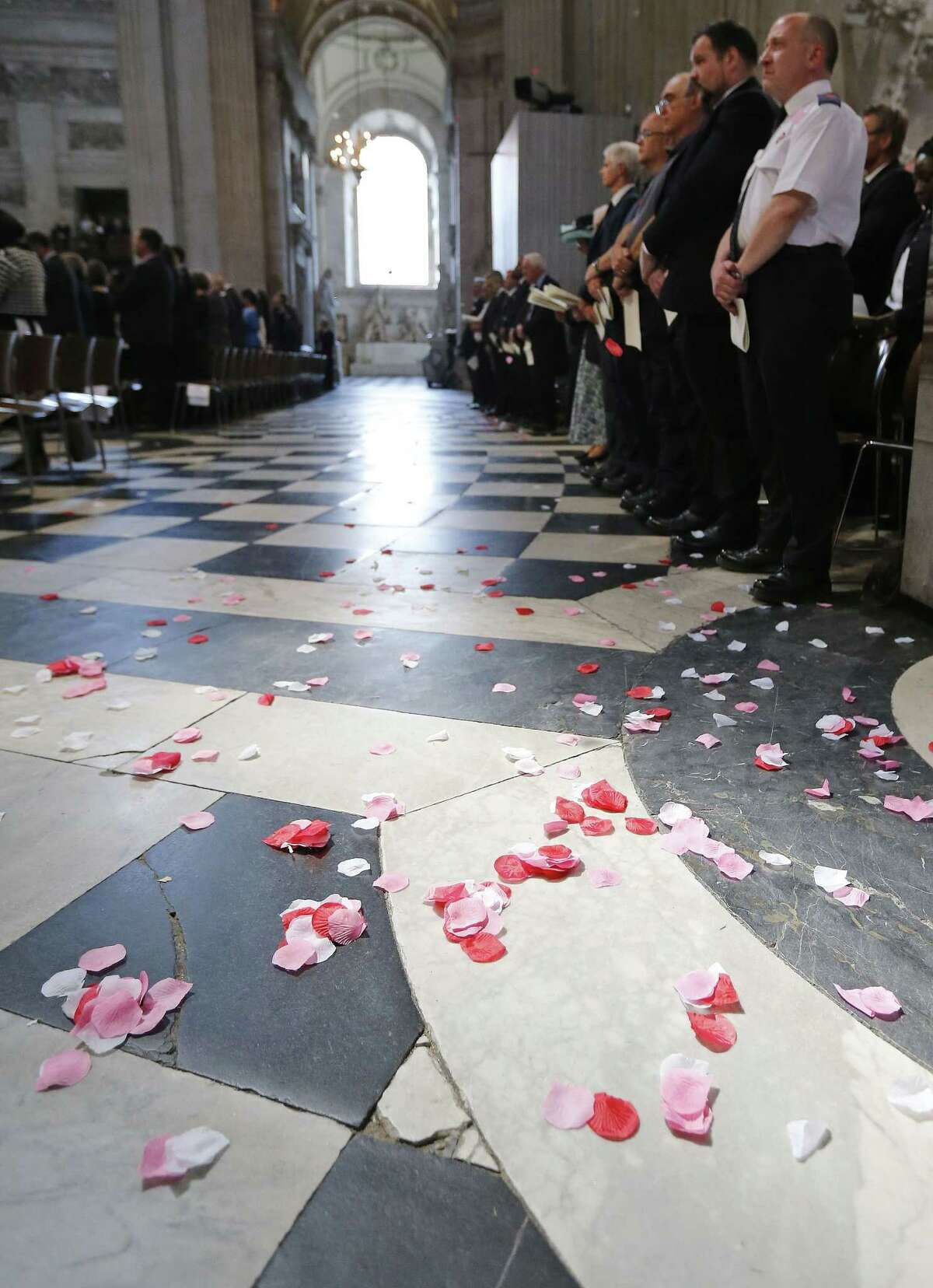 Poppy petals are symbolically scattered on the floor during a service Tuesday, July 7, 2015, in St Paul's Cathedral to commemorate the tenth anniversary of the London Bombings in London.