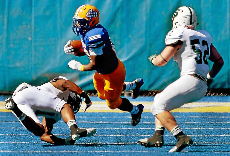 The University of New Haven's Andre Anderson gets tripped up by strong safety Derek Morgan of Slippery Rock during the third quarter Saturday in West Haven. Photo: Peter Hvizdak — Register   / ©2015 Peter Hvizdak