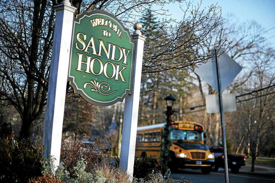 A bus drives past a sign reading Welcome to Sandy Hook on Wednesday, Dec. 4, 2013 in Newtown, Conn. Photo: AP Photo/Jessica Hill   / FR125654 AP