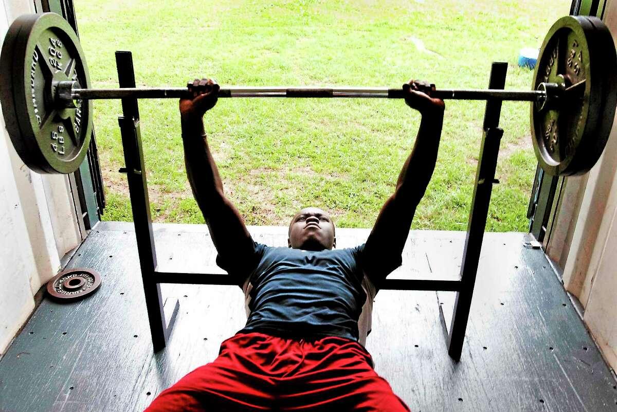 Melanie Stengel — Register ¬ West Haven High School football player, Ervin Phillips, liftse weights during practice 7/15.