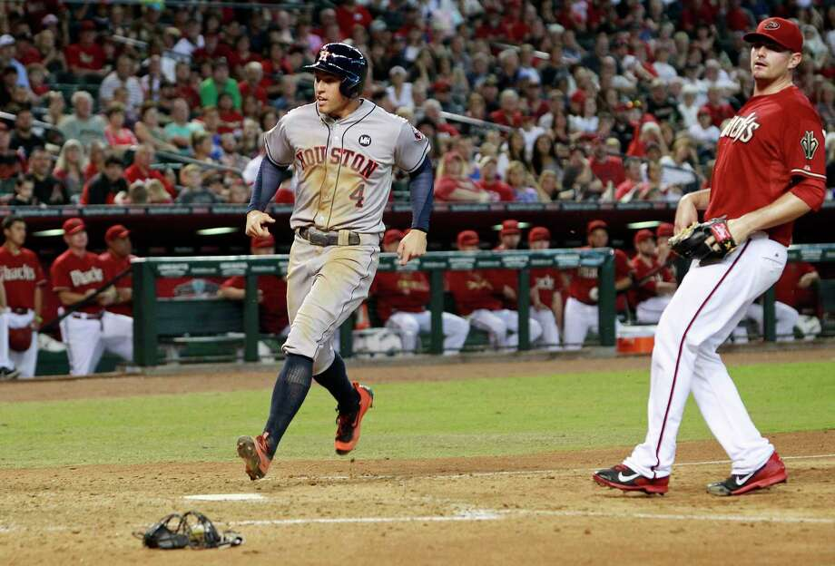 Houston Astros's George Springer (4) crosses the plate to score the game tying run on a wild pitch by Arizona Diamondbacks' Daniel Hudson,right, during the seventh inning of a baseball game, Sunday, Oct. 4, 2015, in Phoenix. (AP Photo/Ralph Freso) Photo: AP / FR170363 AP