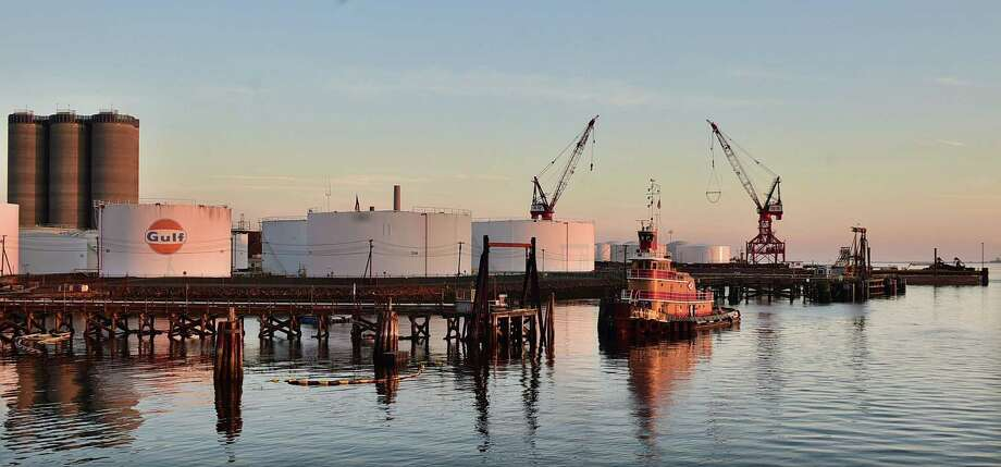 In this May 8, 2105 photo, a tug boat floats near storage tanks at the New Haven Port Authority in New Haven, Conn. New England's ports saw their national rankings in terms of total trade plummet since the 1970s. New Haven, ranked 33rd in the nation in 1972 with 13.1 million tons, ranked 57th in 2013 with only 8.4 million tons, according to the American Association of Port Authorities. Photo: Catherine Avalone/New Haven Register Via AP    / New Haven Register