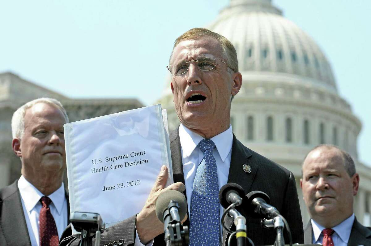 In this 2012 file photo, U.S. Rep. Tim Murphy, R-Pa., center, holds up a copy of the Supreme Court's health care ruling during a news conference by the GOP Doctors Caucus on Capitol Hill in Washington.