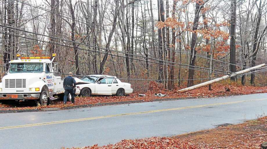 Part of Pool Road in North Haven was shut down for a short time early Thursday after a car crashed into a pole. The pole landed in some nearby wires. Photo: (Wes Duplantier -- New Haven Register)