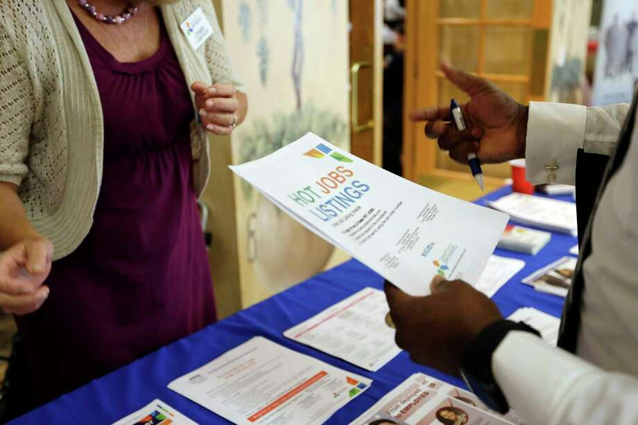 In this Tuesday, Oct. 6, 2015, photo, military veteran Mark Cannon, of Miami, right, talks with Cynthia Carcillo, left, a veterans outreach representative for Career Source Broward, about employment opportunities at a job fair for veterans, in Pembroke Pines, Fla. The number of people seeking U.S. unemployment aid dropped sharply a week earlier, the Labor Department said Wednesday, Nov. 25, 2015, the latest sign that businesses are cutting few jobs. Photo: AP Photo/Lynne Sladky    / AP