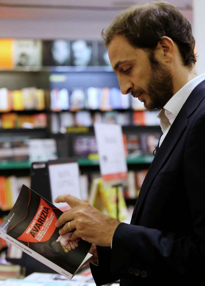 """Italian journalist  Emiliano Fittipaldi browses through his book titled """" Avarice"""" during an interview with The Associated Press, in a Roman bookstore, Tuesday, Nov. 3, 2015. The Vatican's new leaks intensified Tuesday with two books detailing the mismanagement and internal resistance that is thwarting Pope Francis' financial reform efforts: """"Avarice"""" by L'Espresso Vatican reporter Emiliano Fittipaldi and """"Merchants in the Temple"""" by Italian journalist Gianluigi Nuzzi. Photo: AP Photo/Gregorio Borgia    / AP"""