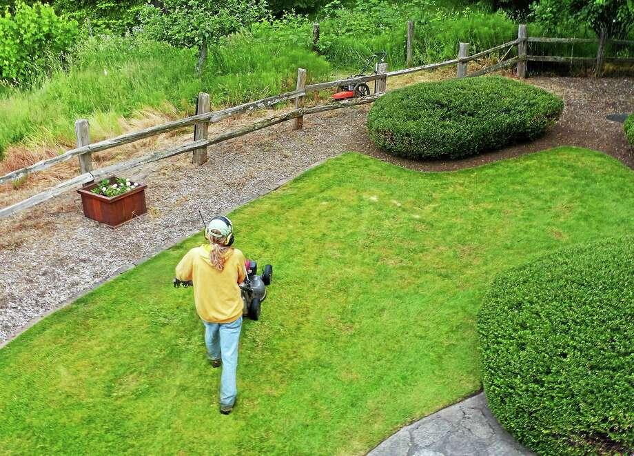 A downsized lawn surrounded by low-maintenance, moisture-saving, weed-smothering mulch on a private residence in Langley, Wash, along with some hardscaping and shrubs, means less grass to mow, less watering and fertilizer use. Photo: Dean Fosdick - The Associated Press   / Dean Fosdick