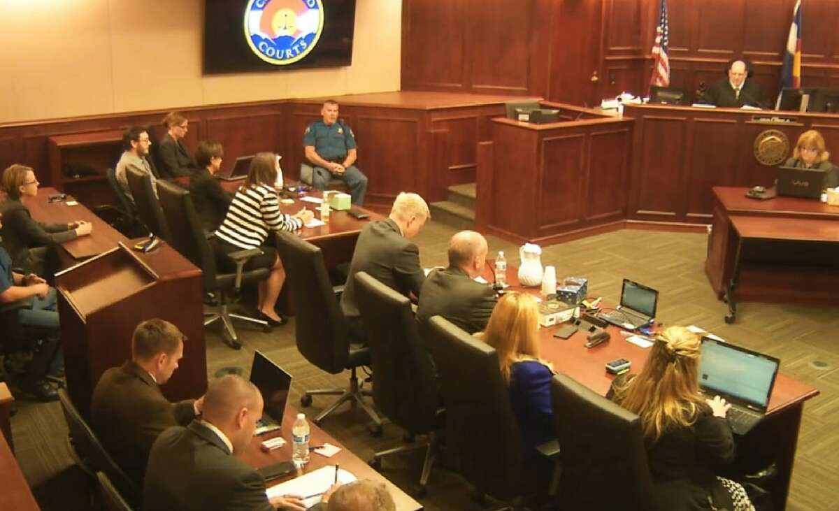 In this image made from Colorado Judicial Department video, James Holmes, top left in tan shirt, watches as Judge Carlos A. Samour, Jr., top right, prepares to read the jury's sentencing verdict in the Colorado theater shooting trial in Centennial, Colo., Friday, Aug. 7, 2015.