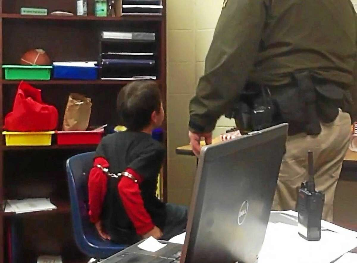 In this image made from video taken in August 2014, an 8-year-old boy struggles and cries out as he sits in a chair with handcuffs around his biceps and his arms locked behind him while a school resource officer stands nearby, at an elementary school in Covington, Ky.