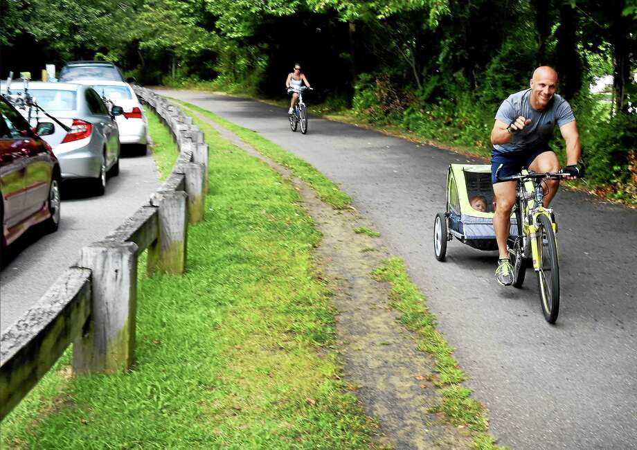 Gary Pavlak of Bristol biking his children Juliana 2, and Jace, 11-months in a kids bike cart, as his  wife Nicole, far left,  follows during an outing along the Farmington Canal Trail by Todd Street near Whitney Ave. in Hamden Sunday August 30, 2015. Photo: (Peter Hvizdak — New Haven Register)   / ©2015 Peter Hvizdak