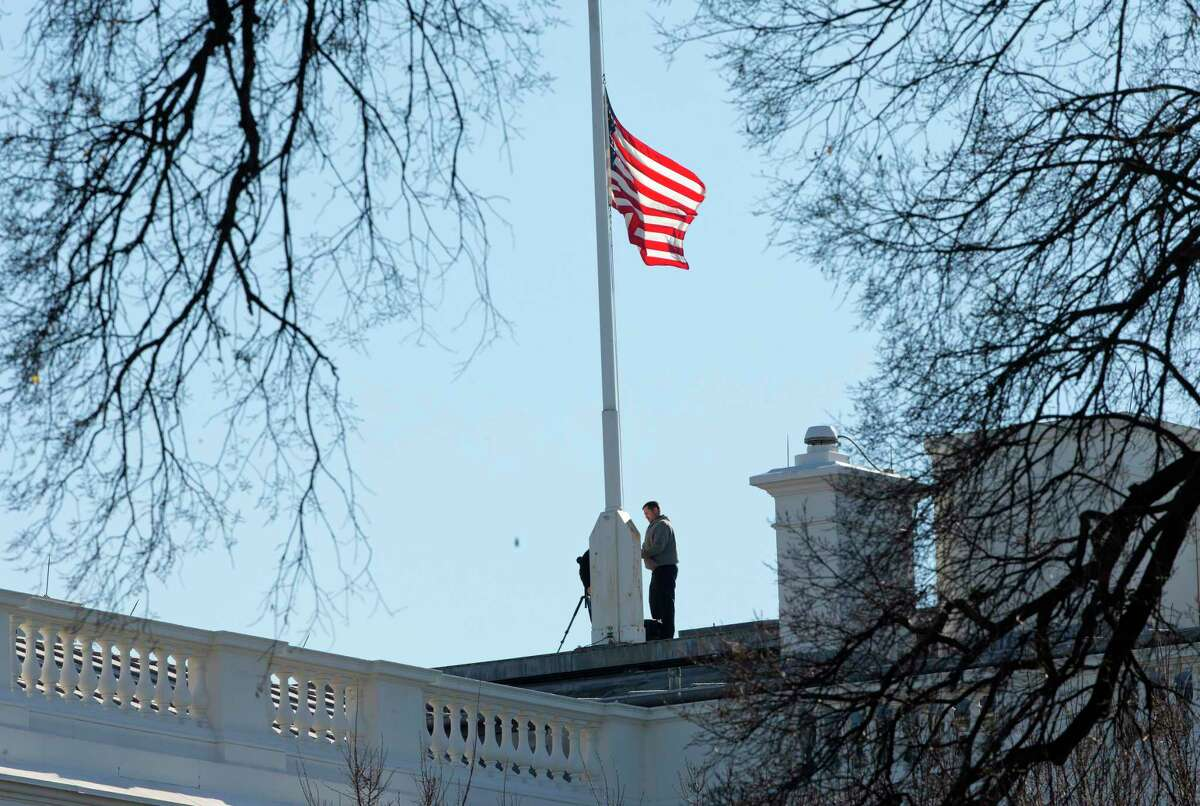 Workers lower the American flag above the White House in Washington, Thursday, Dec. 3, 2015. President Barack Obama ordered that flags be lowered at all government buildings to honor the victims of yesterday's mass shooting in San Bernardino, Calif.