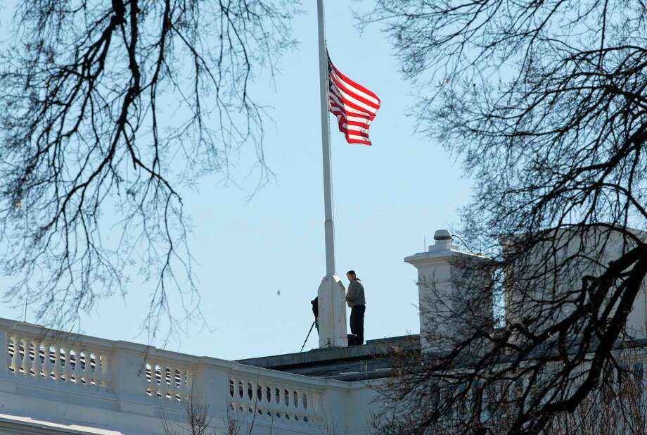 Workers lower the American flag above the White House in Washington, Thursday, Dec. 3, 2015. President Barack Obama ordered that flags be lowered at all government buildings to honor the victims of yesterday's mass shooting in San Bernardino, Calif. Photo: AP Photo/Pablo Martinez Monsivais    / AP