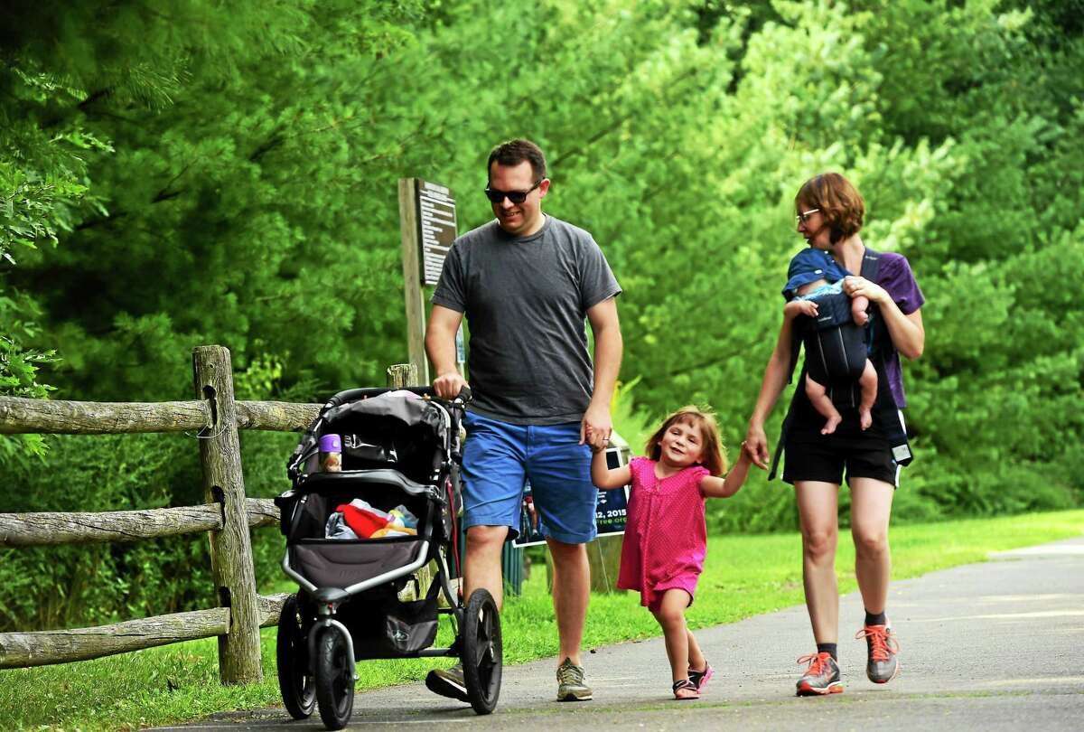 Aaron Hawthorne of Hamden, left, with his daughter Emily, 3, son Alex, 2 months, and wife, Katie Hawthorne, walking along the Farmington Canal Trail by Sherman Avenue near Whitney Avenue in Hamden.