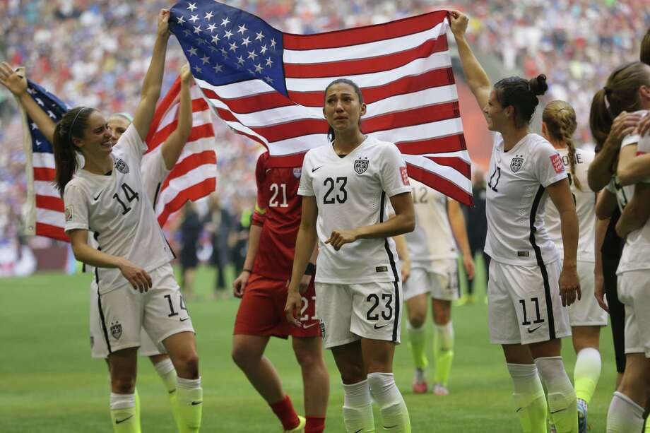 The United States' Morgan Brian (14), Christen Press (23), and Ali Krieger (11) celebrate with the U.S. flag after the U.S. beat Japan 5-2 in the Women's World Cup final on Sunday. Photo: Elaine Thompson — The Associated Press   / AP