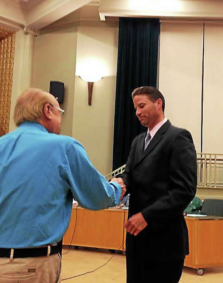 Connecticut Classic Chevy Club President George Civitelli presents a check for $4,000 to Police Chief Thomas Wyrda to go toward the purchase of an ATV to be used to respond to calls on the Farmington Canal Trail. Photo: Kate Ramunni — New Haven Register