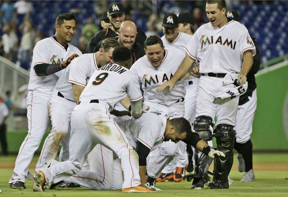 Miami Marlins' Martin Prado, kneeling, is mobbed by teammates after hitting a double to score Christian Yelich for the win during the 11th inning of a baseball game against the New York Mets, Friday, Sept. 4, 2015, in Miami. The Marlins won 6-5. (AP Photo/Wilfredo Lee) Photo: AP / AP