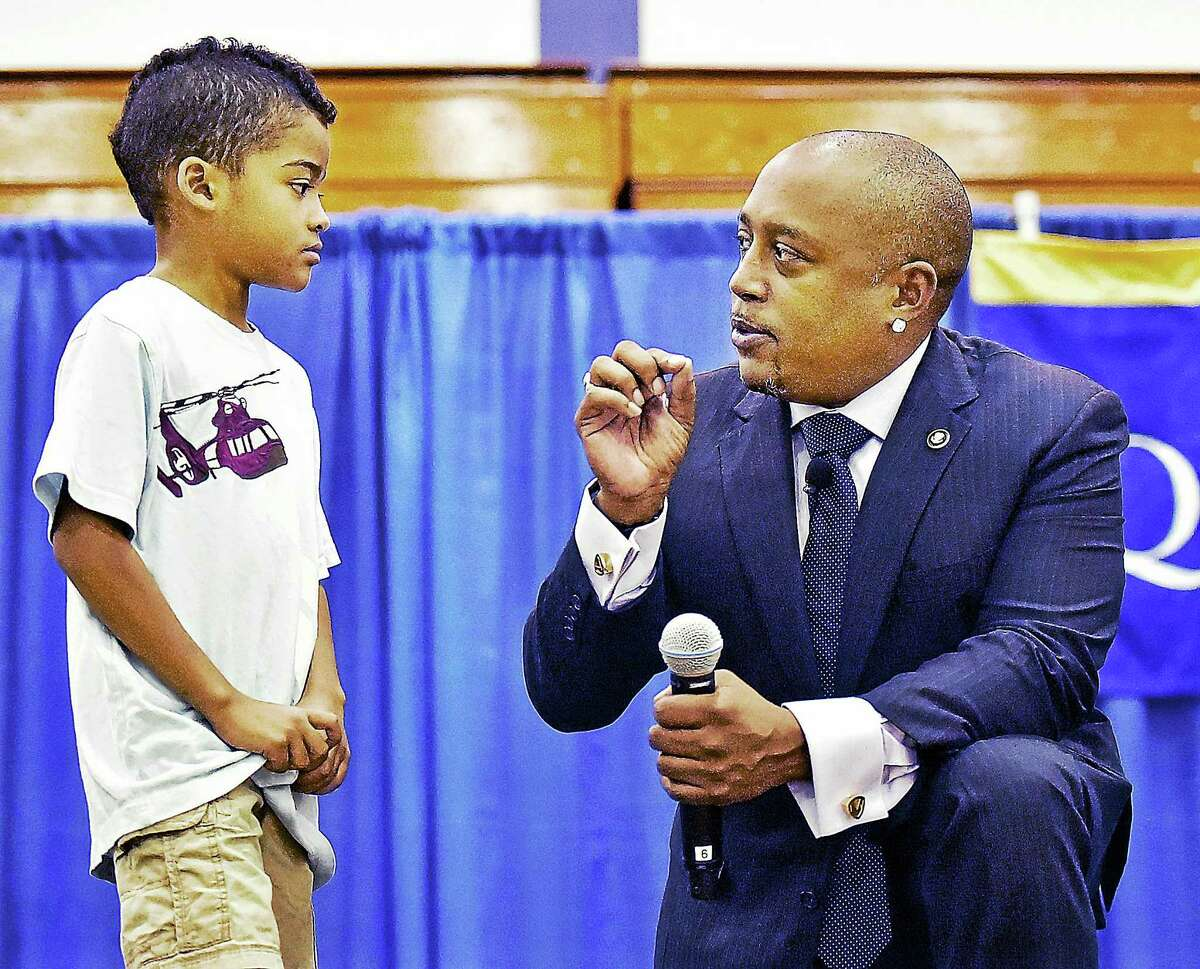 """Daymond John of ABC's reality business show, """"Shark Tank,"""" gives seven-year-old Brian Johnson, of Meriden entrepreneurial advice at the end of the Q&A portion of Tuesday's event. Brian asked John what he could do to become more successful at selling erasers to his schoolmates when all his classmates are using tablets."""