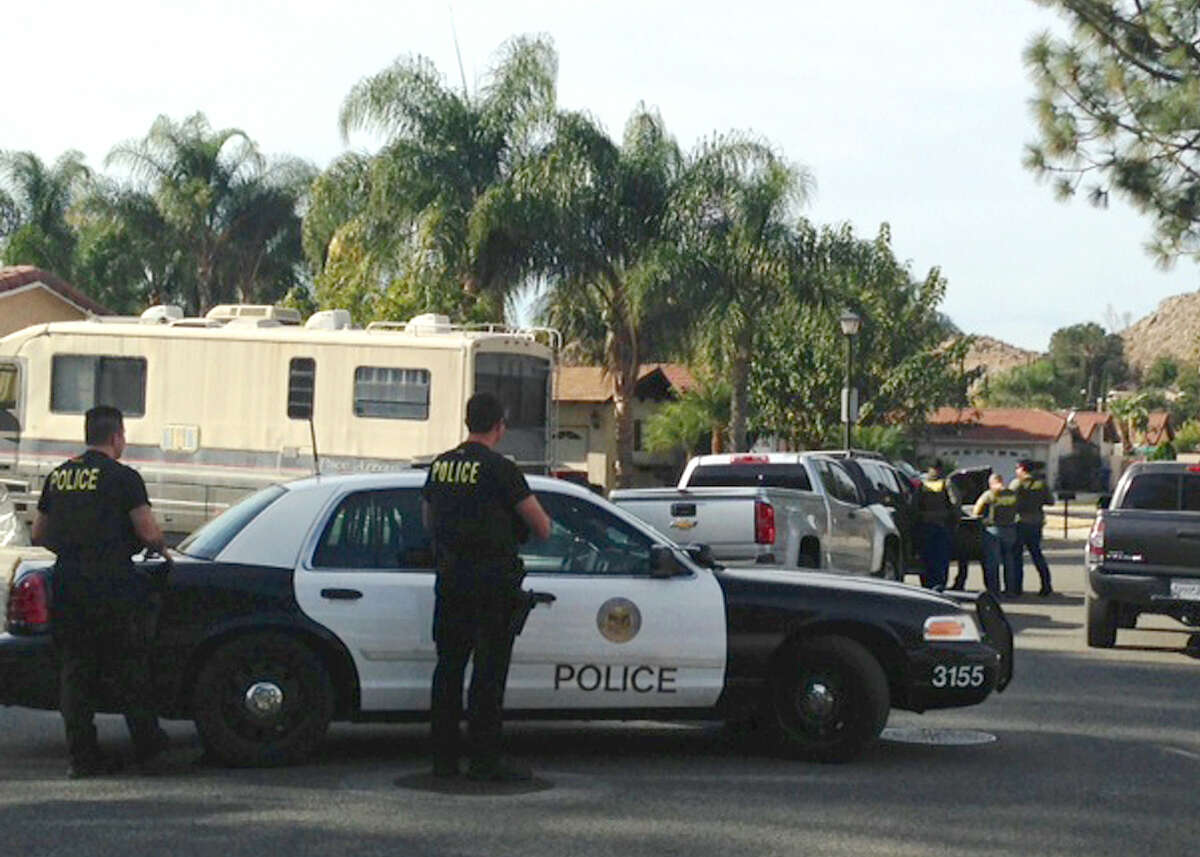 Police surround a home in Riverside, Calif., Thursday, searching for evidence in connection with Wednesday's shootings in San Bernardino.