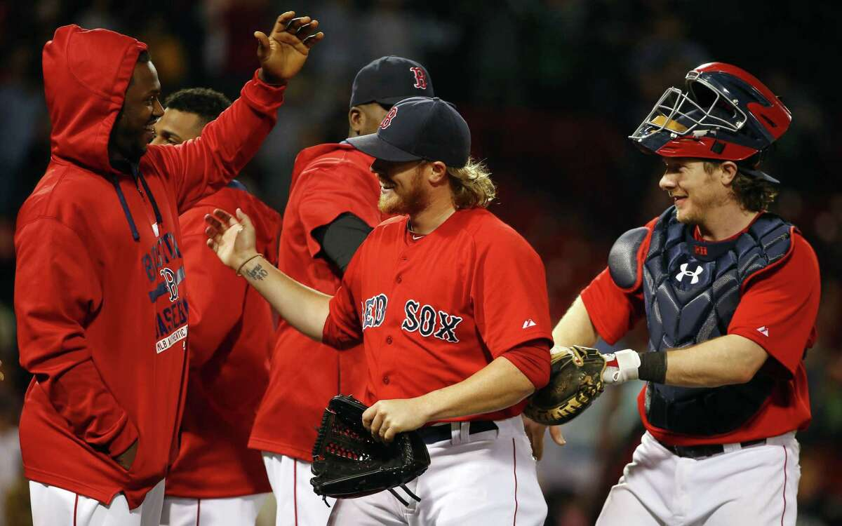 Boston Red Sox relief pitcher Robbie Ross Jr., center, is congratulated by teammates including catcher Ryan Hanigan, right, after striking out Philadelphia Phillies' Ryan Howard to end the game during the ninth inning of the Boston Red Sox 7-5 win over the Philadelphia Phillies in a baseball game at Fenway Park in Boston Friday, Sept. 4, 2015. (AP Photo/Winslow Townson)