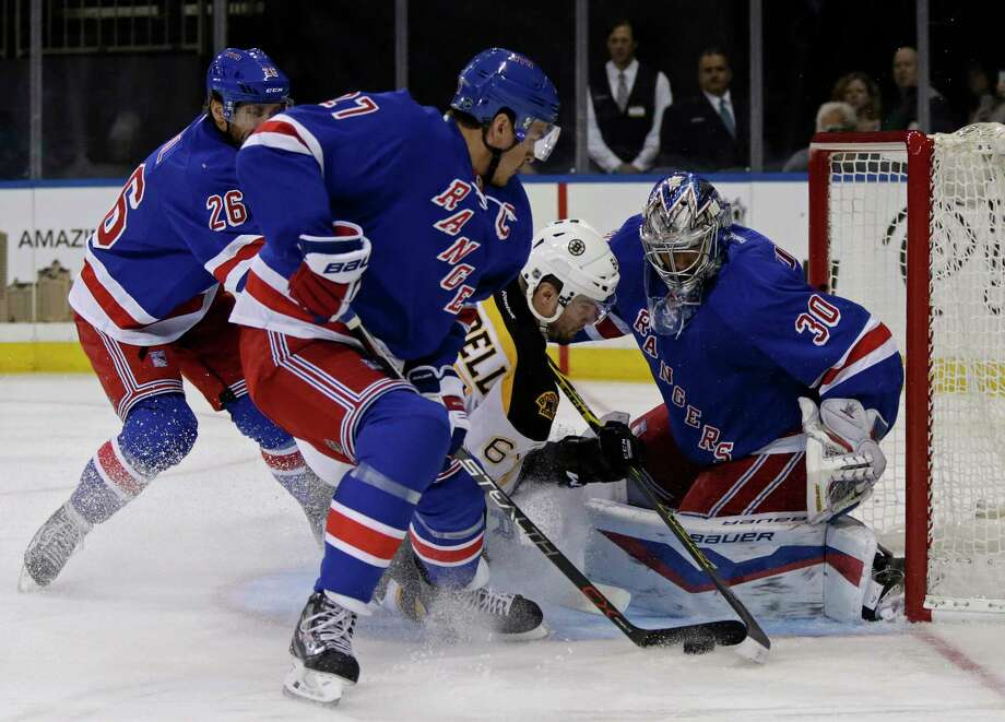 New York Rangers goalie Henrik Lundqvist (30) makes a save on a shot by Boston Bruins right wing Tyler Randell (64) as Rangers defenseman Ryan McDonagh (27) looks on during the first period of an NHL preseason hockey game at Madison Square Garden in New York, Wednesday, Sept. 30, 2015. (AP Photo/Adam Hunger) Photo: AP / FR110666 AP