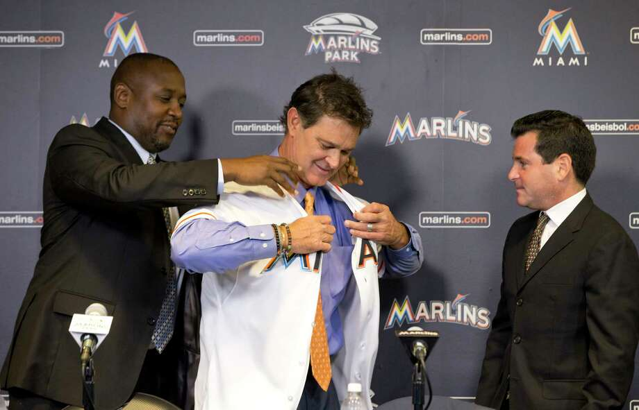 Michael Hill, left, president of baseball operations for the Miami Marlins, helps Don Mattingly put on a jersey as team president David Samson, right, looks on after Mattingly was introduced as manager on Monday in Miami. Photo: Wilfredo Lee — The Associated Press   / AP