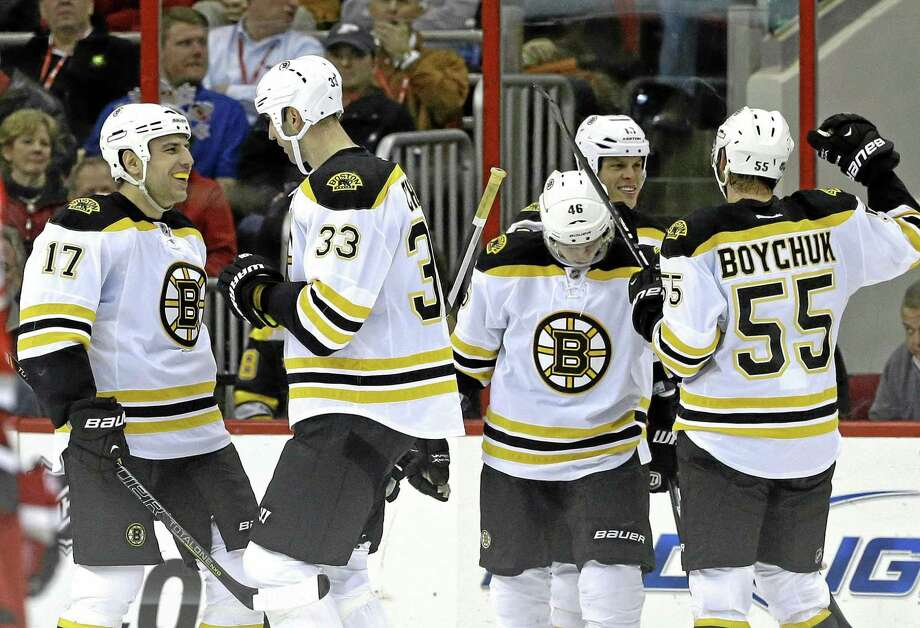 Boston Bruins' Milan Lucic (17), Zdeno Chara (33), of Slovakia, David Krejci (46), of the Czech Republic, and Johnny Boychuk (55) celebrate with Nathan Horton, rear, following Horton's goal against the Carolina Hurricanes during the second period of an NHL hockey game in Raleigh, N.C., Monday, Jan. 28, 2013. Boston won 5-3. (AP Photo/Gerry Broome) Photo: AP / AP